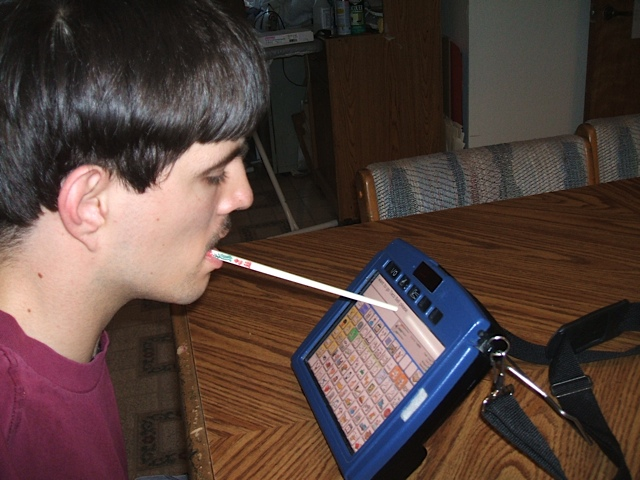 Kolya uses a chop stick to make his selections on his device since he does not have arms
