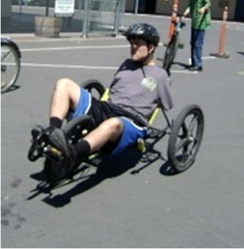 Kolya rides a specially built bike which he steers by leaning and can brake without the use of hand brakes