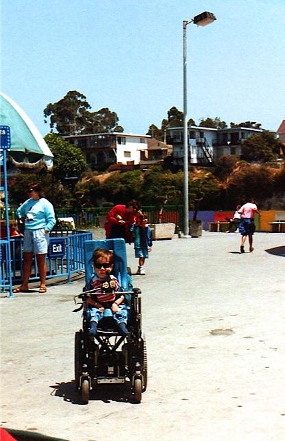Kyle motoring around Santa Cruz Boardwalk with his shades