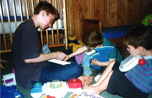 Photo - Cousin Marc changing batteries in his toys as Kolya looks on.